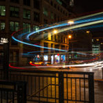 Monument London Underground station and London Bridge at night as the traffic streaks by